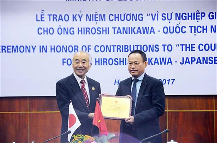 Presenting insignia for the cause of education to Hiroshi Tanikawa