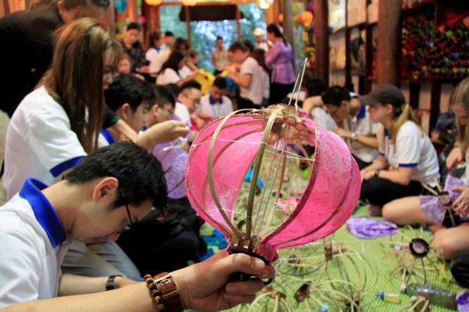 APEC delegates make decorative multi-coloured lanterns in Hoi An